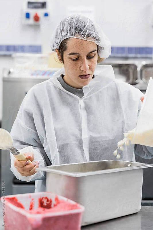 Female worker with sterile clothing working in ice cream factory by Lior + Lone for Stocksy United