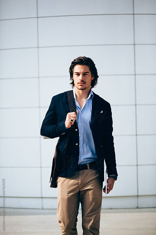 Young business man walking out of the office by michela ravasio for Stocksy United