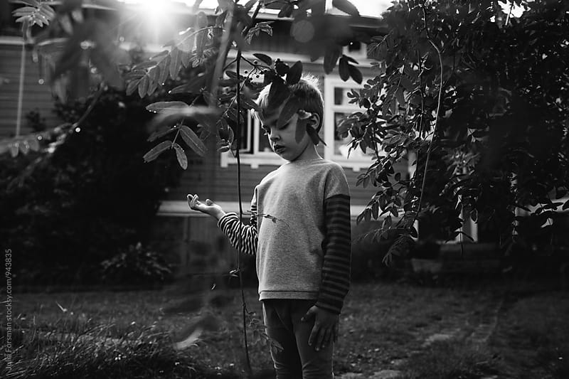 Young boy closes his eyes and holds his hand out while playing in a garden. by Julia Forsman for Stocksy United