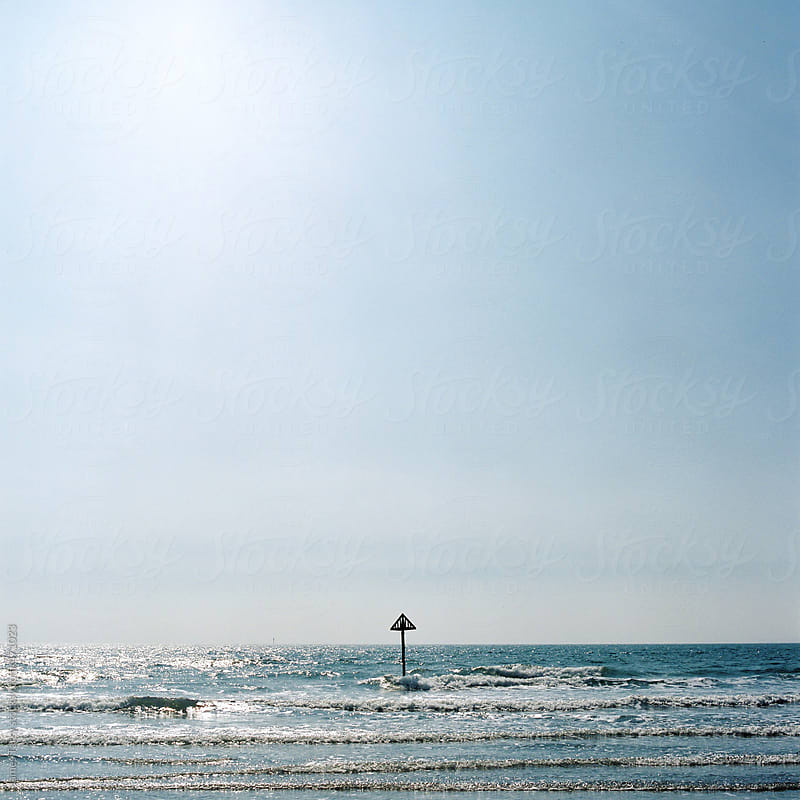 Big sky, sea, small pole!  by James Tarry for Stocksy United