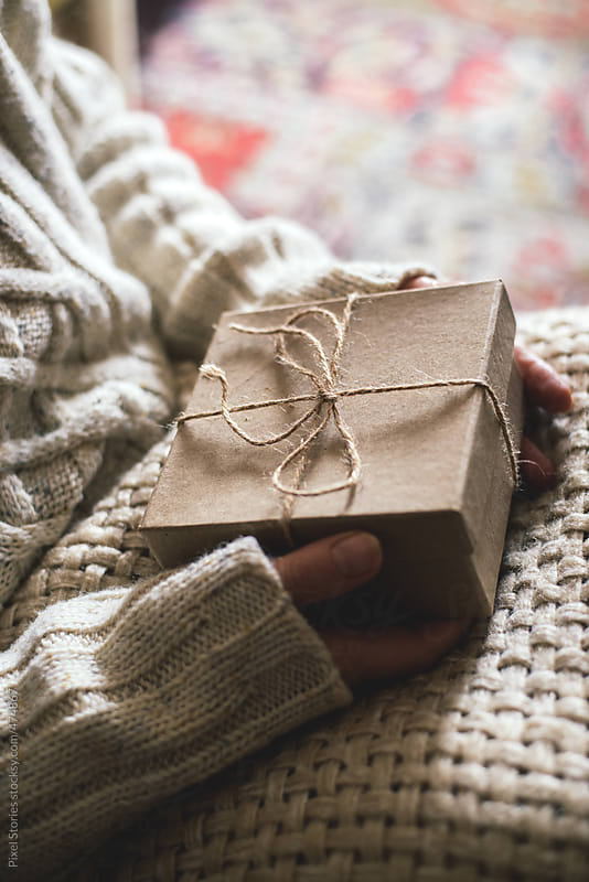 Woman covered with warm blanket holding a rustic present by Pixel Stories for Stocksy United