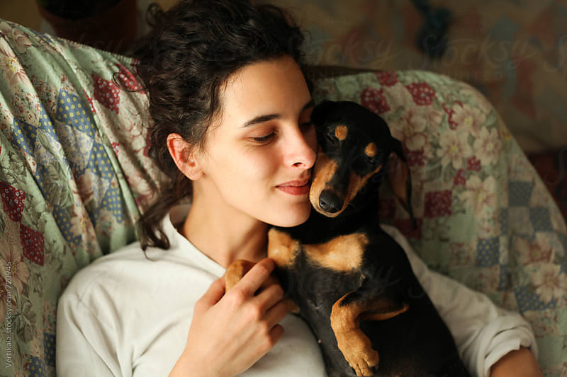 Young woman and her small black dog hugging on the couch. From above. by Marija Mandic for Stocksy United