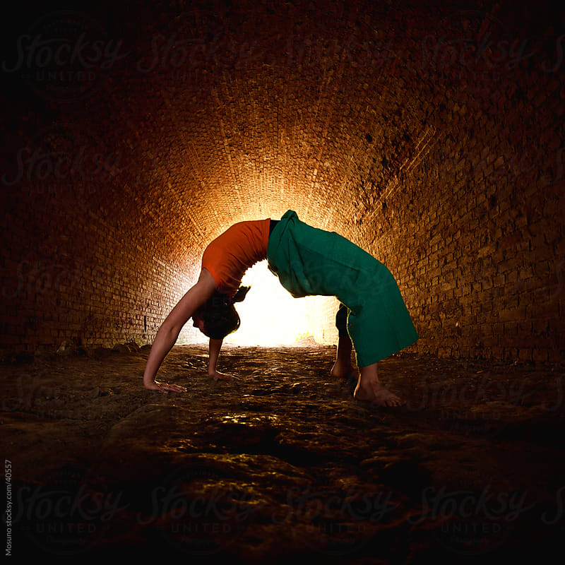 Young woman doing yoga in the dark tunnel. by Mosuno for Stocksy United