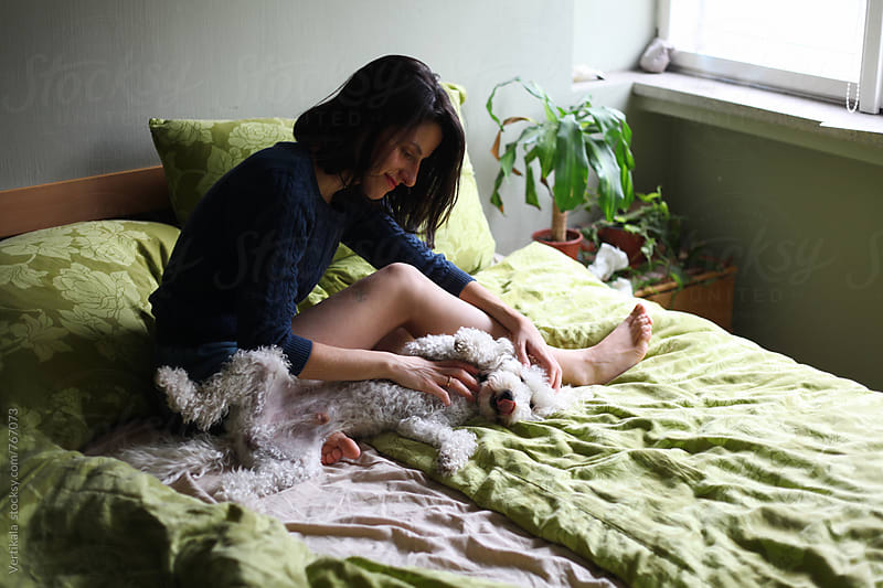 Woman cuddling with her white dog on the bed   by Marija Mandic for Stocksy United