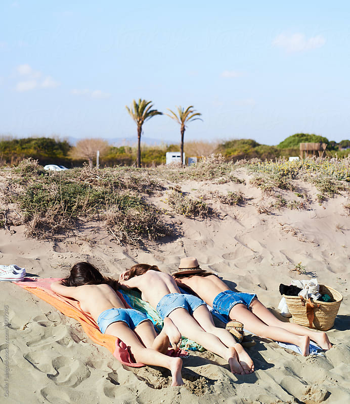 Three girls on beach blanket getting tanned by Guille Faingold for Stocksy United