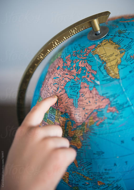 Child points to Canada on a globe by Cara Dolan for Stocksy United