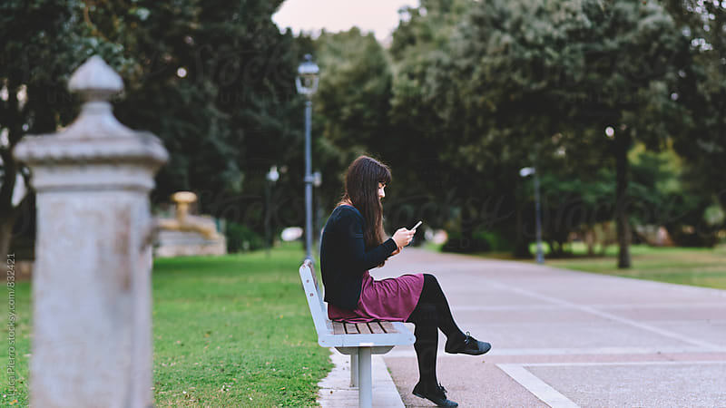 Woman  using a smart phone in a city park sitting on a bench by Luca Pierro for Stocksy United