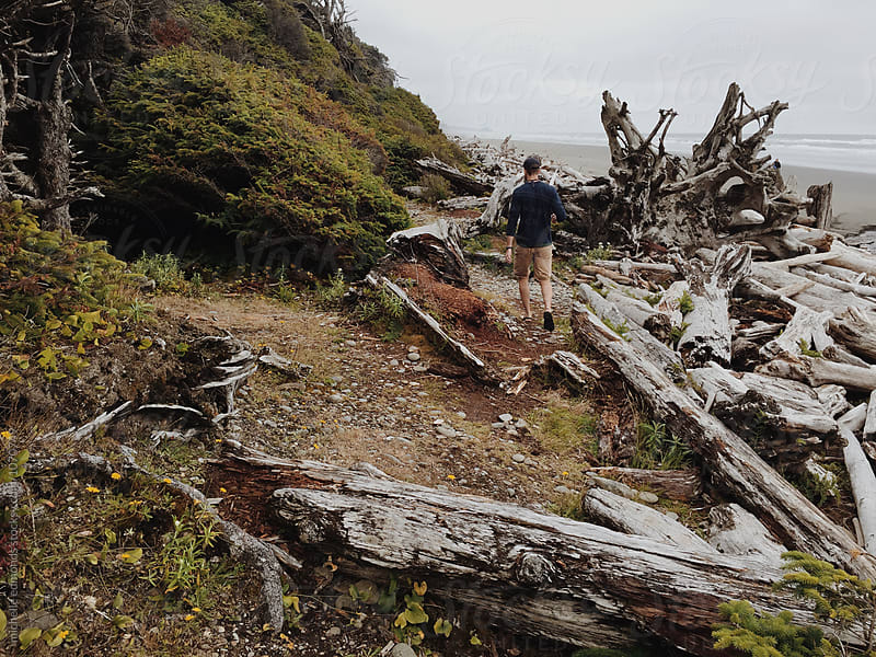 Male Hiker Standing on Driftwood on the Pacific Shore in Washington by michelle edmonds for Stocksy United