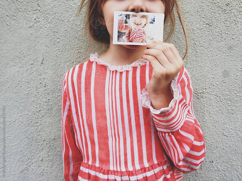 Young girl holding Polaroid in front of f mouth by Kristin Rogers Photography for Stocksy United