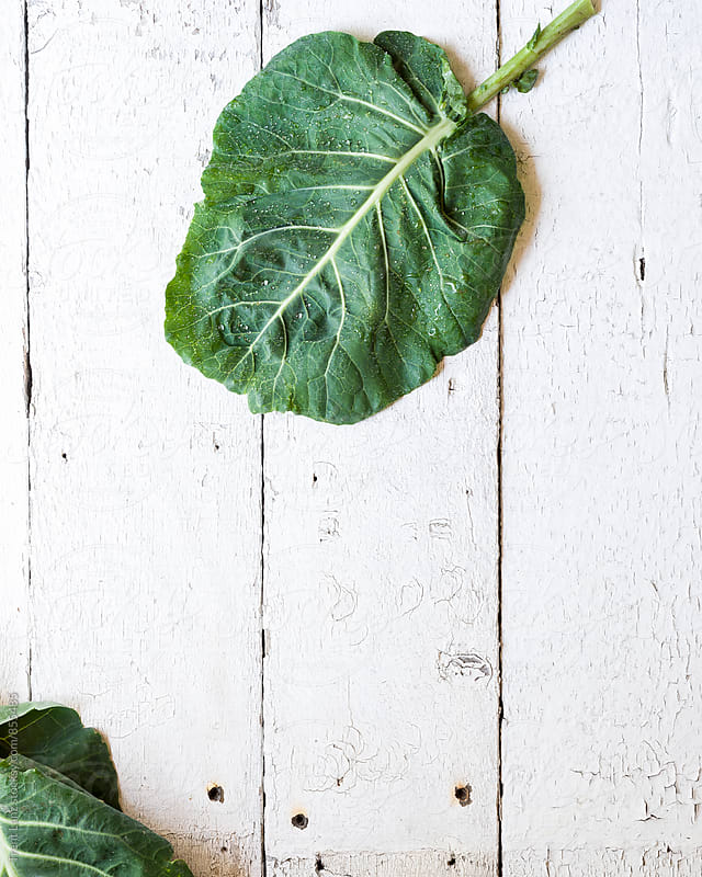Leaf of Collard greens salad on shabby wooden background by Trent Lanz for Stocksy United