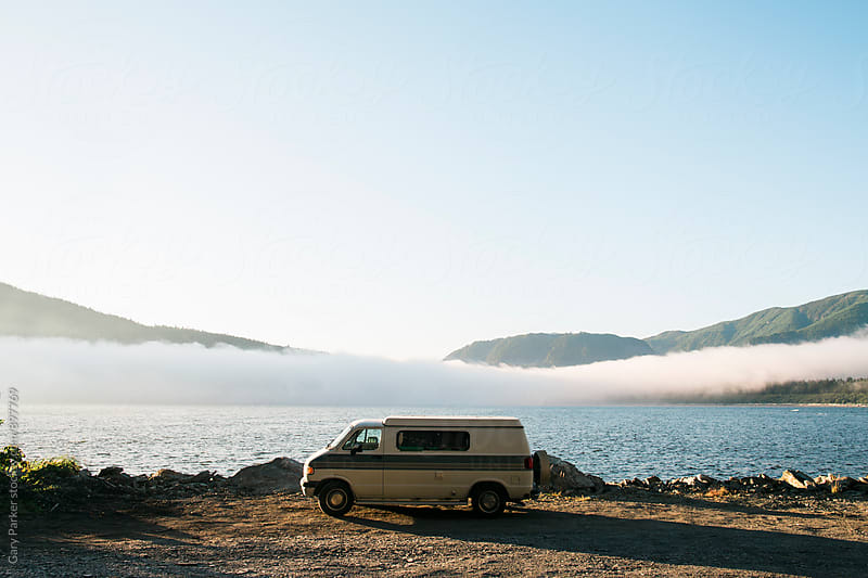 Van parked in front of the ocean with fog bank and mountains  by Gary Parker for Stocksy United
