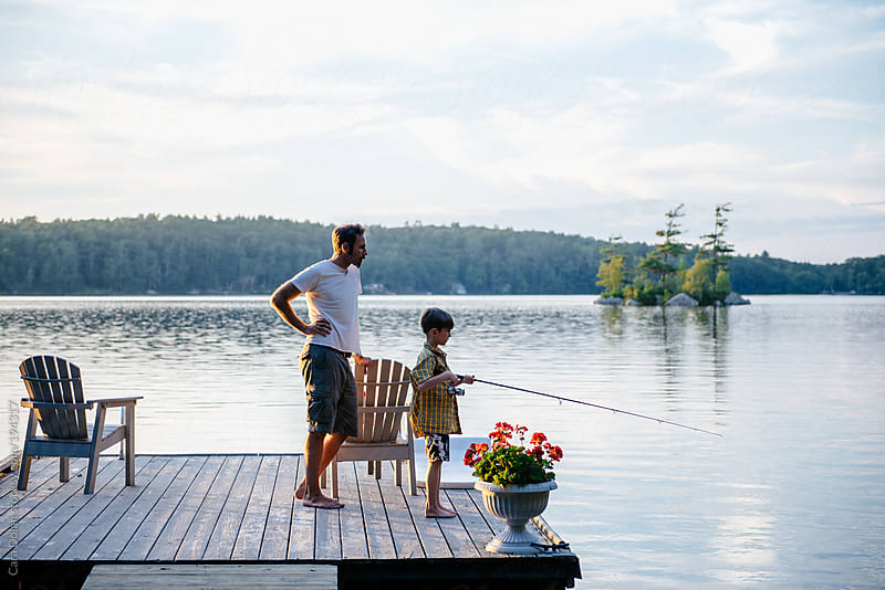 Father and son out at the lake together on a summer evening by Cara Dolan for Stocksy United