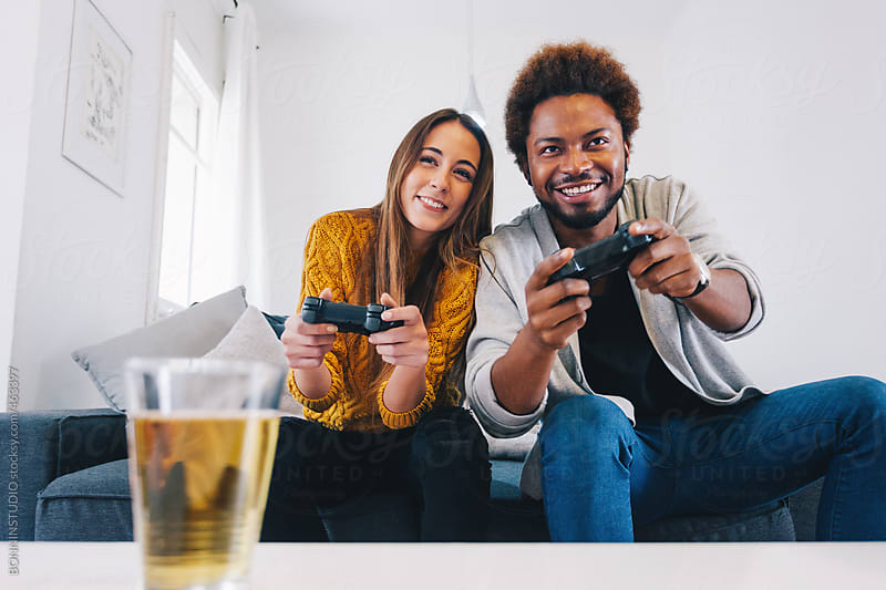 Two young friends playing video games at home. by BONNINSTUDIO for Stocksy United