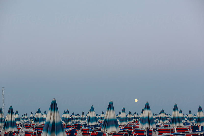 Closed beach umbrellas in a bathhouse after sunset by michela ravasio for Stocksy United