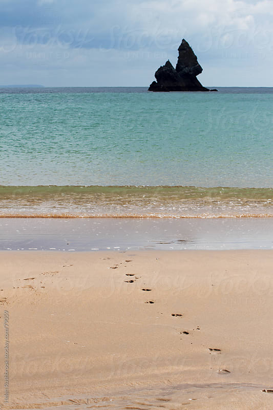 Footprints in sand leading into an azure-blue sea by Helen Rushbrook for Stocksy United