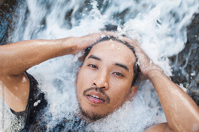 Young asian man cooling off on a waterfall. by Shikhar Bhattarai for Stocksy United