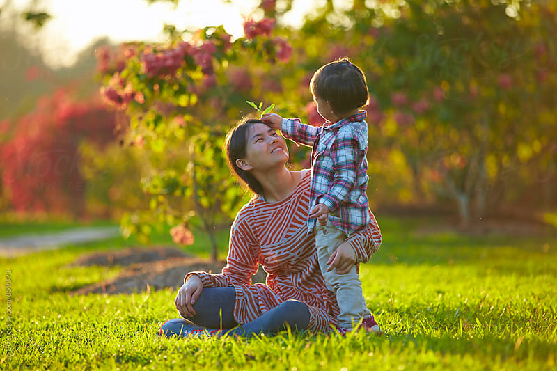 happy asian kid with her mother in the park by cuiyan Liu for Stocksy United