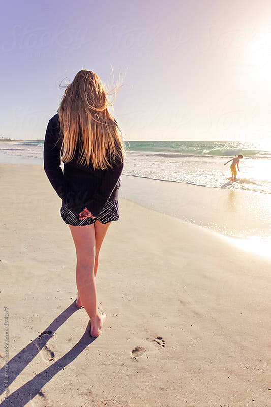 Teen girl walking at the beach watching her brother rides his skim board by Angela Lumsden for Stocksy United