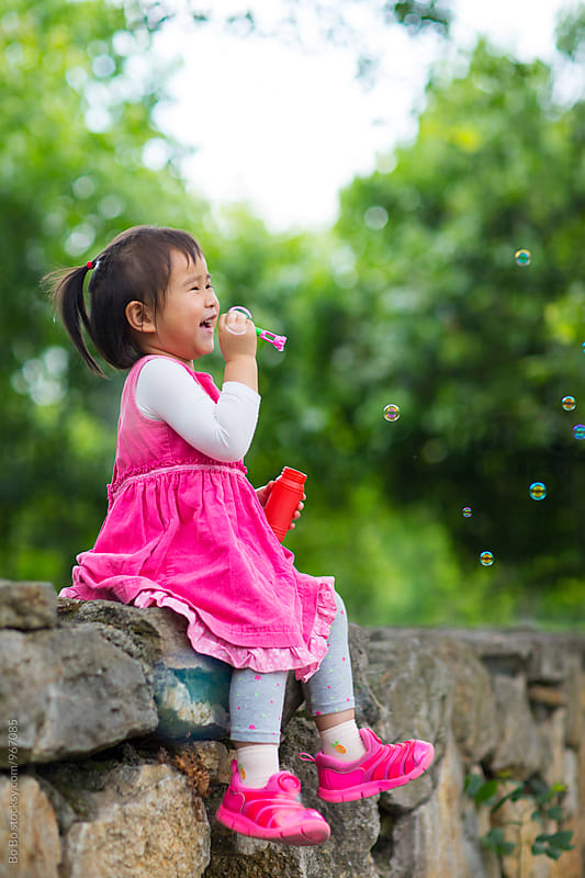 happy little aisan girl blowing soap bubble by cuiyan Liu for Stocksy United