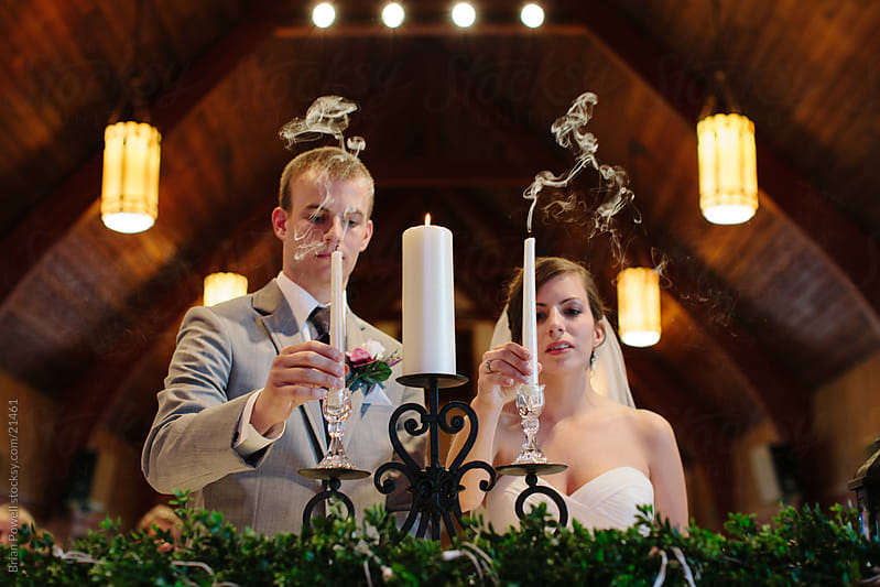 bride and groom with unity candle by Brian Powell for Stocksy United
