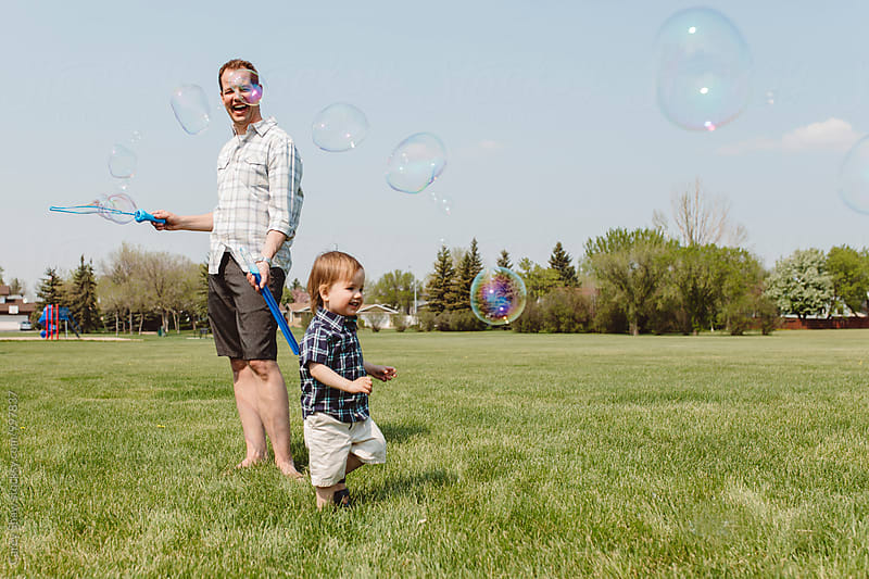 Father and son playing outdoors with bubble by Carey Shaw for Stocksy United