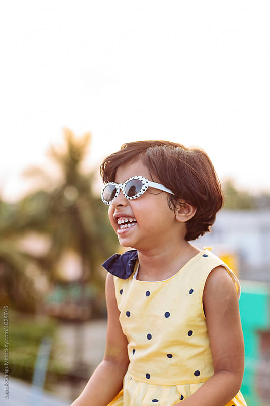 Smiling portrait of cute little girl wearing sunglasses by Saptak Ganguly for Stocksy United