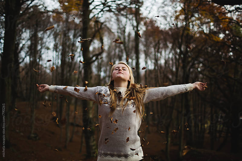 Falling leaves of a girl with open arms by michela ravasio for Stocksy United