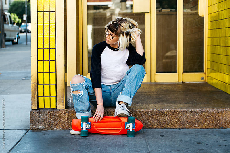 Young woman sits on store front porch with skateboard for a rest by Jesse Morrow for Stocksy United