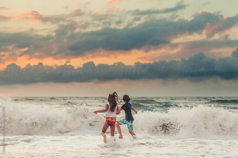 Kids running into the waves in the ocean during sunset by Cindy Prins for Stocksy United