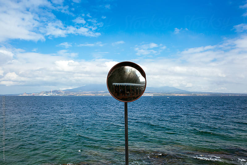 Safety mirror found along a blind curve of a coastal road.  by Lawrence del Mundo for Stocksy United