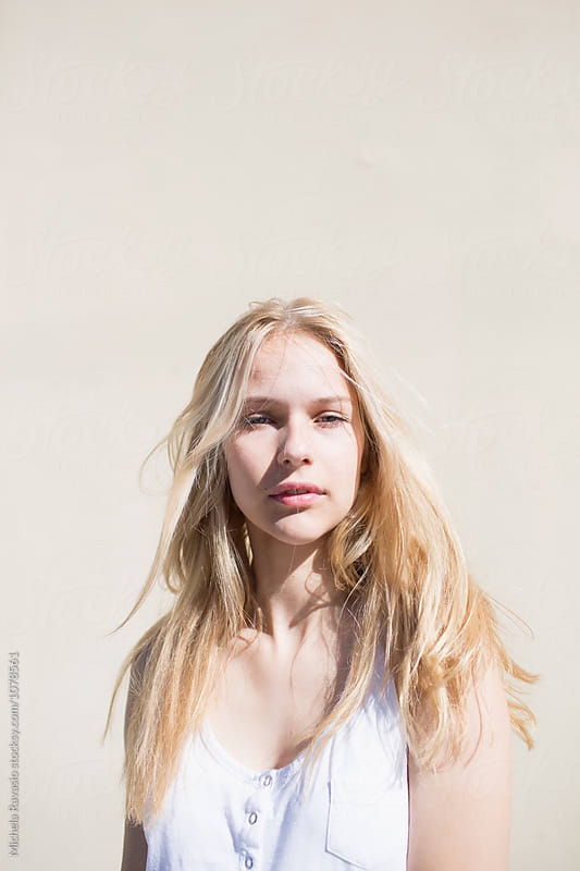 Blonde candid girl against yellow wall by michela ravasio for Stocksy United