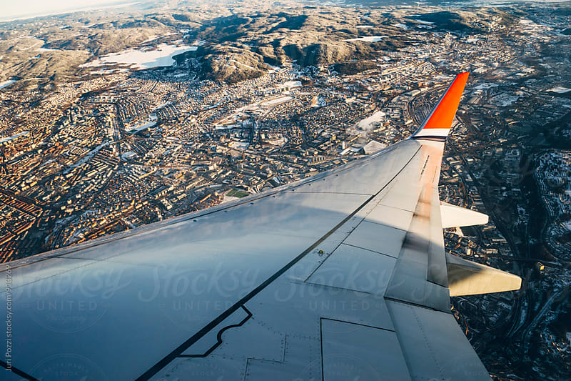 Airplane flying over Oslo City  by Juri Pozzi for Stocksy United