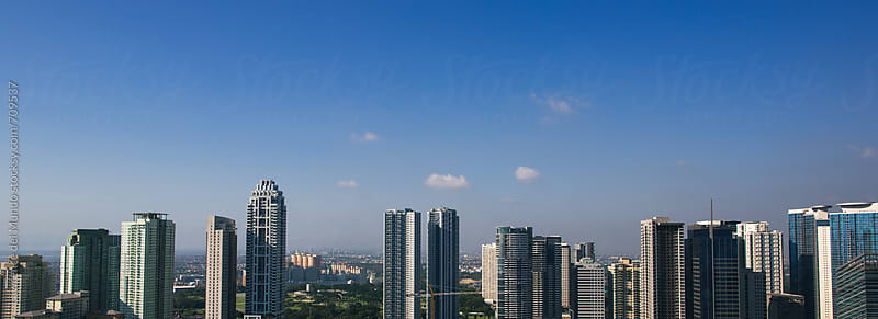 Panoramic view of an up and coming city skyline by Lawrence del Mundo for Stocksy United