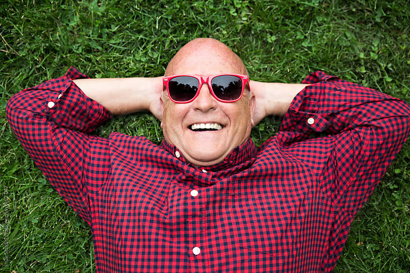 Cheerful senior man in sunglasses on green grass by Inuk Studio for Stocksy United