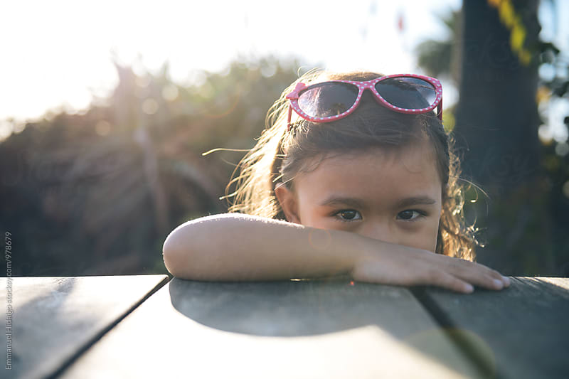 Cute little girl playfully peeks her head above a picnic table by Emmanuel Hidalgo for Stocksy United