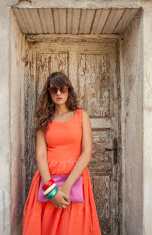 Woman in an orange dress standing against old wooden door. by Mosuno for Stocksy United