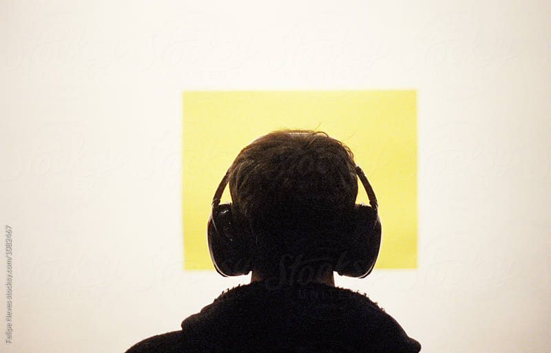 Person wearing headphones looking at a yellow rectangle by Felipe Neves for Stocksy United