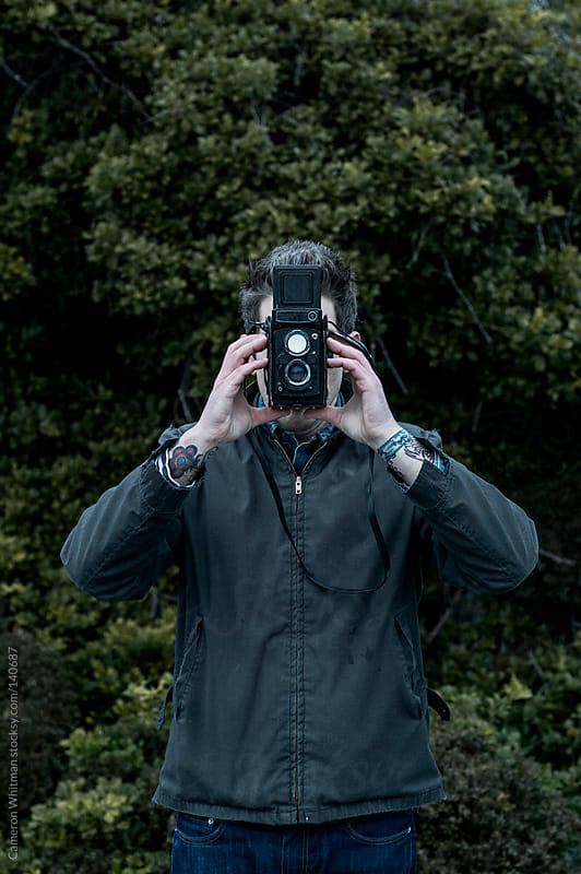 Man covering face with his camera.  by Cameron Whitman for Stocksy United