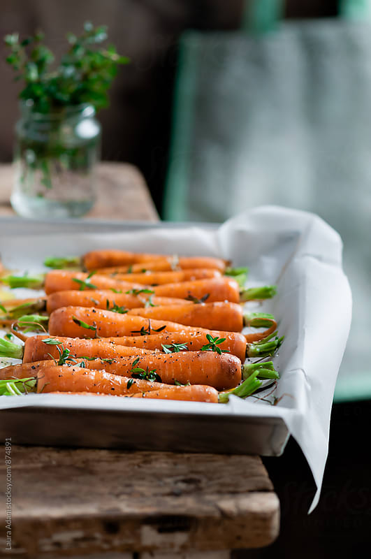 Food: carrots ready to be baked with honey and thyme by Laura Adani for Stocksy United
