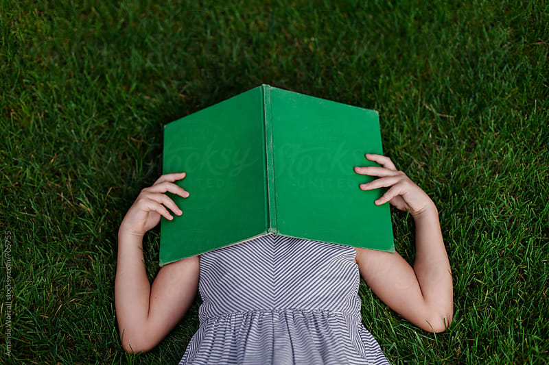 School girl laying in grass with a green, vintage book over her head by Amanda Worrall for Stocksy United
