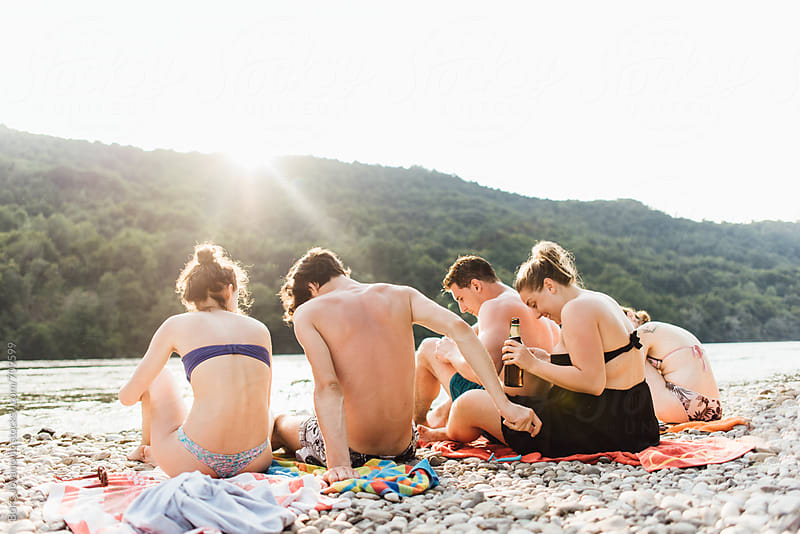 Group of friends enjoying a day at the river beach by Boris Jovanovic for Stocksy United