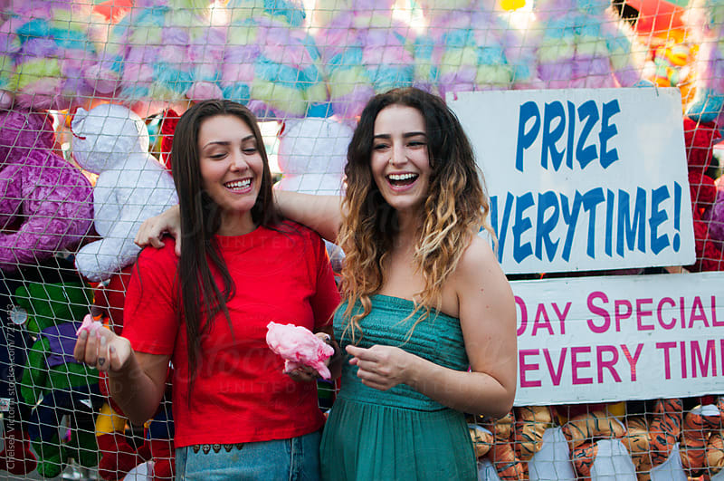 Young friends eating cotton candy at a carnival by Chelsea Victoria for Stocksy United