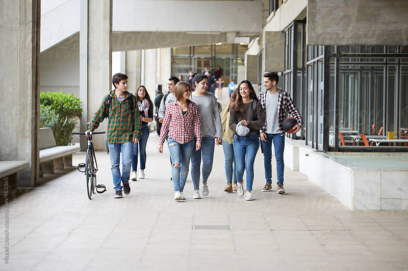 Group of young students walking towards de camera in the campus by Miquel Llonch for Stocksy United