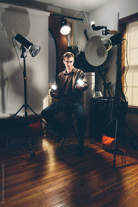 photographer  in studio with gear by Brian Powell for Stocksy United