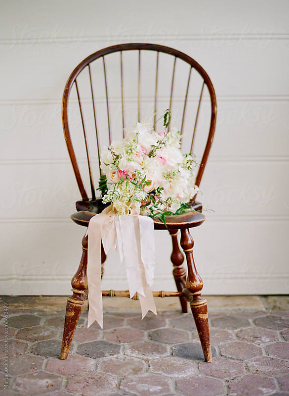 Bridal bouquet on an antique chair by Marta Locklear for Stocksy United