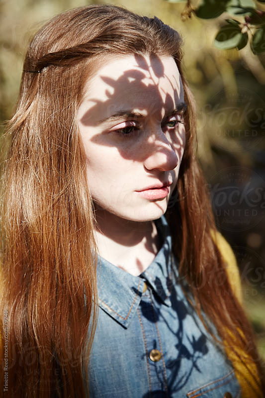 Woman in nature with shadows on her face by Trinette Reed for Stocksy United