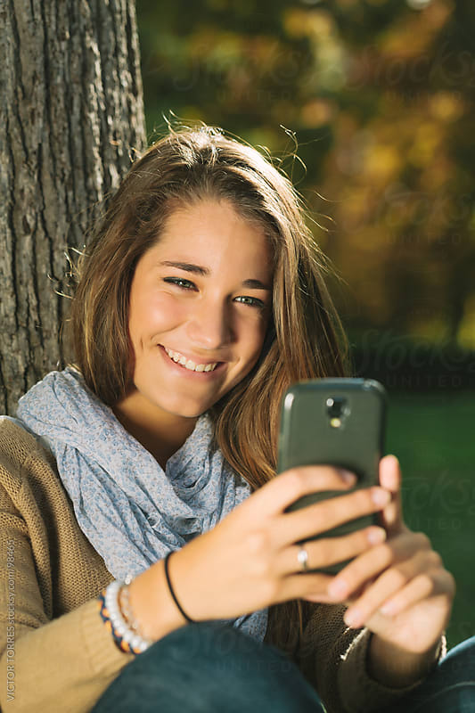 Cute Teenager Having a Video Call in the Park by VICTOR TORRES for Stocksy United