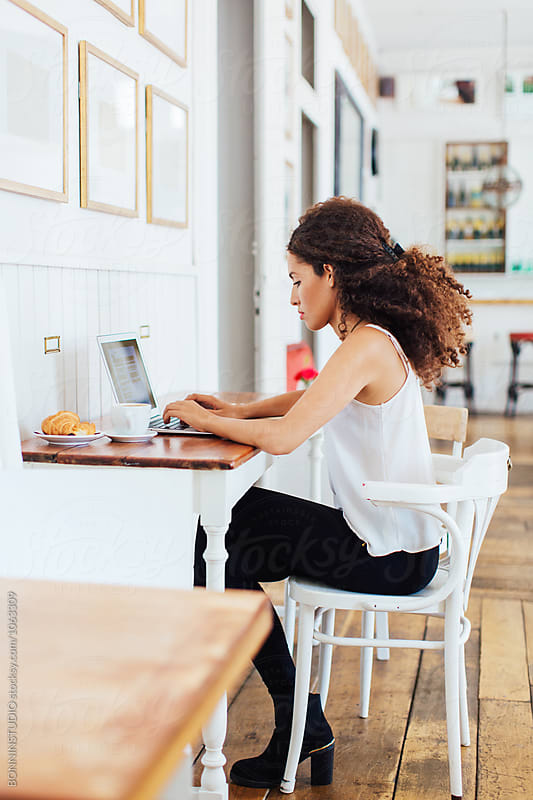 Side view of a businesswoman working on her laptop in a coffee bar.  by BONNINSTUDIO for Stocksy United