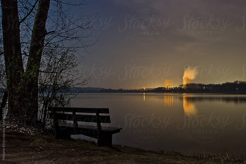 Bench at calm lake looking towards a power plant by Melanie Kintz for Stocksy United