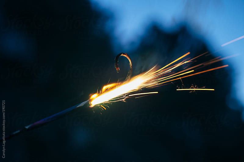 Sparkler - sparks flying out against the dark sky by Carolyn Lagattuta for Stocksy United